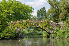 Picturesque stone bridge, Central Park, NYC. People and tourists walking across a picturesque stone bridge, Central Park, NYC spanning a tranquil pond in a stock images