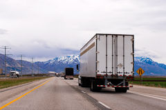 Picturesque straight highway trucks trailers snow capped mountai Stock Photo