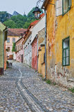 Picturesque street in Sighisoara, Romania. Old cobblestone street with pastell coloured buildings in Transylvania royalty free stock photos