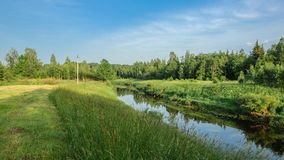 A picturesque summer landscape. A narrow river with a sloping meadow and dense forest on high coasts. A picturesque summer landscape. A narrow river with a Stock Images