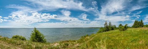 summer landscape. panoramic view of the lake under a beautiful cloudy sky with a coast in the foreground royalty free stock photography