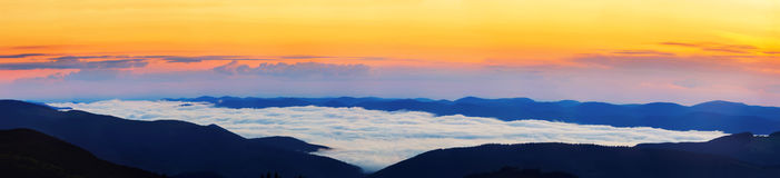 Picturesque sunrise morning in mountains above clouds, Carpathians, panoramic view, Ukraine. Royalty Free Stock Photo