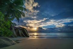 Sunset on paradise beach at anse georgette, praslin, seychelles. Picturesque sunset on dream beach at anse georgette on praslin on the seychelles. A big granite stock image