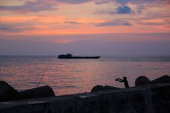 Picturesque sunset near the sea with ship, rocks, horizon, fisherman and orange clouds. Phu Quoc, Vietnam. Picturesque sunset near sea ship rocks horizon stock images