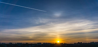 Picturesque sunset over the city and a track of a departing plane in the sky Royalty Free Stock Photos
