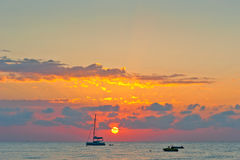Picturesque sunset sky over the sea and the silhouettes of boats Royalty Free Stock Photography