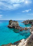 Sunshiny Faraglioni at Torre Sant Andrea, Italy. Picturesque sunshiny seascape with cliffs, rocky arch and stacks faraglioni, at Torre Sant Andrea, Salento sea Stock Photography