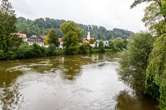 Picturesque town on a forested river bank. Picturesque town nestling amongst green trees on a forested river bank viewed across the water Stock Images