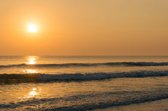 Picturesque tropical sunrise over sand beach. Golden color sky and sea water with soft waves seascape Royalty Free Stock Image