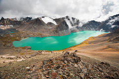 Picturesque turquoise mountain lake Ala-Kul. Alakol lake with cloudy sky. Tien Shan. Kyrgyzstan. Stock Photography