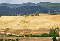 Picturesque Tuscany landscape with rolling hills, valleys, sunny fields, cypress trees, rural road, houses on a hill. Royalty Free Stock Photo