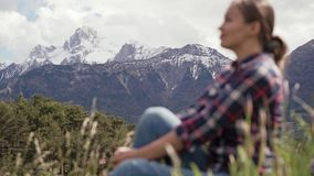 Picturesque view of Alps mountains and blurred image of tourist woman sitting on a green meadow. Travel in Alps. Mountains 4k stock footage