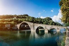 Picturesque view of medieval stone arch bridge Ponte della Maddalena across river Serchio in Borgo a Mozzano, Lucca, Tuscany,. Italy. Scenic travel destination royalty free stock images