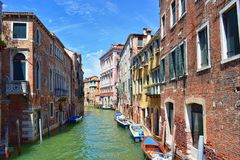 Picturesque view of narrow Venetian canal with anchored boats Stock Photo