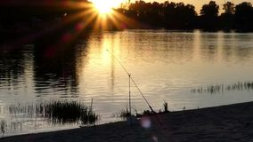 A forest lake with a sipping fixed for fishing at sunset in summer. A picturesque view of a nice lake in the dusk of sunset with one spinning fixed to catch fish stock video footage
