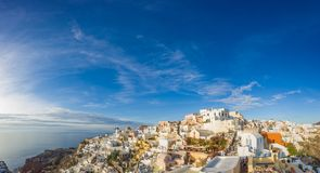Picturesque view, Old Town of Oia or Ia on the island Santorini. White houses, windmills and church with blue domes at sunset, Greece Royalty Free Stock Photography