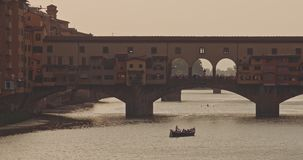 The picturesque view of Ponte Vecchio at sunset. The view of Ponte Vecchio, the famous Arno river bridge from Uffizi Gallery. Also known as `Old Bridge`, it is stock video footage