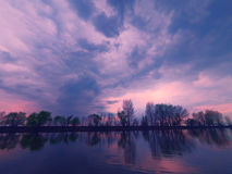 Picturesque view of the river with reflections of the trees on far riverbank. Dramatic evening scene under stormy rainy Royalty Free Stock Image