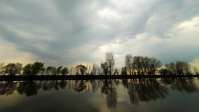 Picturesque view of the river with reflections of the trees on far riverbank. Dramatic evening scene under stormy rainy. Clouds. Rain is startinag and rare stock video