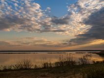 Picturesque view of the river at sunset with cloudy sky. In spring evening Royalty Free Stock Photography