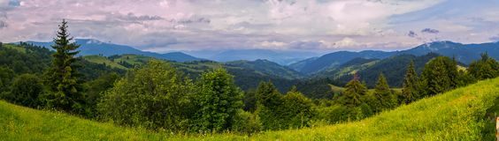 A picturesque view of the vast endless green Carpathian mountains against the blue sky with white clouds royalty free stock photography