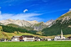 Picturesque Village of Livigno in Italian Alps. Picturesque Village of Livigno in Green Mountain Valley with Quaint Buildings and Church Steeple in Foothills of Stock Photos