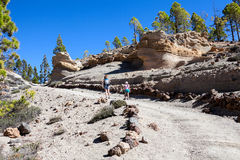 Picturesque volcanic rocks are on footpath to Lunar landscape. A woman with her daughter hiking on a mountain path. Tenerife, Cana Stock Image