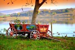 Picturesque wagon autumn beautiful lakeside. Picturesque decorated wagon on autumn colored beautiful green grass lakeside. ducks floating at lake , Bulgaria Stock Photo