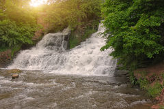 Picturesque waterfall in the forest at sunset Royalty Free Stock Image