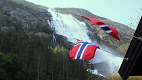 Picturesque waterfall Langfoss in Norway. Two views of picturesque waterfall Langfoss in Norway with Norwegian flags on foreground. National tourist route stock video footage