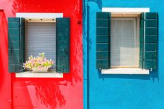 Picturesque windows with shutters on red and blue wall on the fa. Mous island Burano, Venice, Italy Stock Image