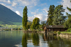 Picturesque wooden boat house on a lake shore royalty free stock photography