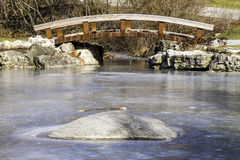 Picturesque wooden footbridge over a frozen winter pond, rock. In foreground Stock Images