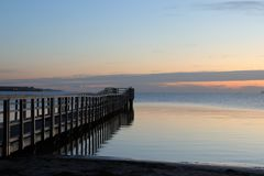 Picturesque wooden jetty at dawn. The photo shows a wooden jetty at the Baltic Sea in the early morning at dawn Stock Photo