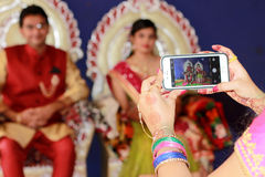 Picturing couple - India. Capturing memories of ring ceremony in mobile phone Royalty Free Stock Images