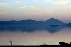 Picturing lake prespa in macedonia on sunset. Pisture of a men picturing   lake prespa in macedonia on sunset Stock Photo