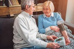 A picutre of happy old couple that like to be together. THe woma. A picutre of happy old couple that like to be together. THe women is measuring her blood Stock Photography