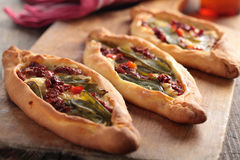 Pide. Turkish pides with vegetables on a wooden cutting board Stock Photo