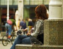 Pidgeon, das von der Hand des Mädchens isst Stockfoto