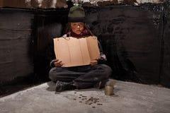 Pidiendo al niño sin hogar que se sienta con una muestra en blanco y algo cambie Imagenes de archivo