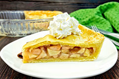 Pie apple with whipped cream in plate on board. Classic American apple pie with whipped cream in a plate, napkin on a wooden boards background Royalty Free Stock Image
