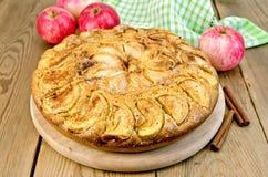 Pie apple whole on a blackboard. A sweet whole apple pie, napkin, cinnamon on a wooden boards background Royalty Free Stock Photo