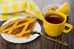 Pie with apricot jam, teaspoon, tea, sugar and lemon. On wooden table Royalty Free Stock Images