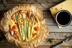 Pie with asparagus and tomatoes on wooden rustic table. Royalty Free Stock Photos