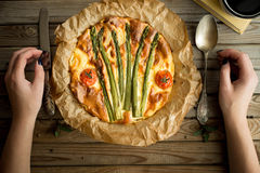 Pie with asparagus and tomatoes on wooden rustic table. Royalty Free Stock Photo