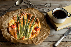 Pie with asparagus and tomatoes on wooden rustic table. Stock Photography