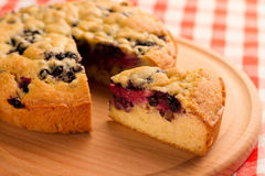 Pie with berries. Cut a piece of cake with berries on a wooden chopping board and a checkered napkin Stock Photo