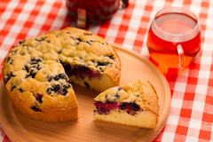 Pie with berries. Cut a piece of cake with berries on a wooden chopping board and a checkered napkin with a cup of tea Stock Image