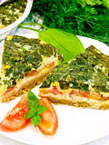 Pie celtic with spinach and tomato in plate on board Royalty Free Stock Images