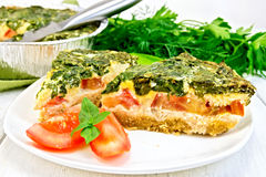 Pie celtic with spinach and tomato in plate on table Stock Photos